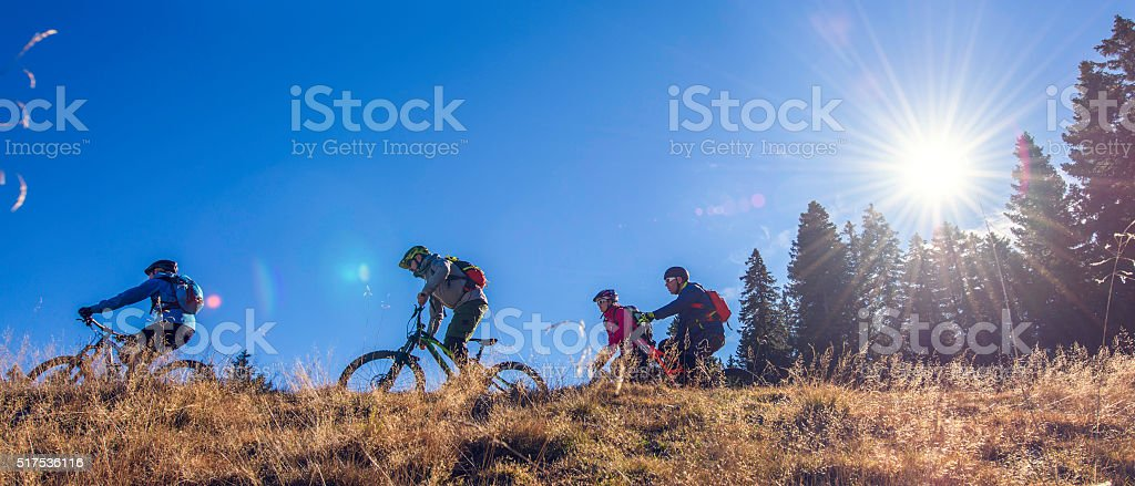 Four cyclists riding their bikes on top of a hill stock photo