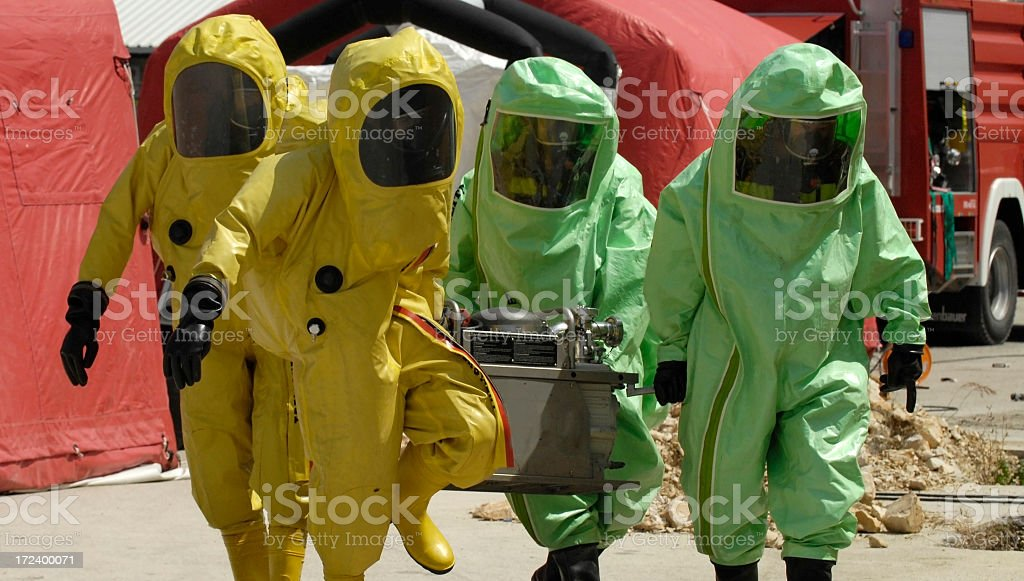 Four decontamination operatives at work in green and yellow stock photo