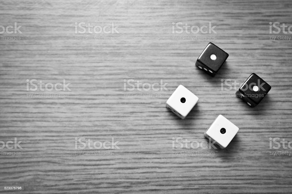 Four dice on a wooden table stock photo