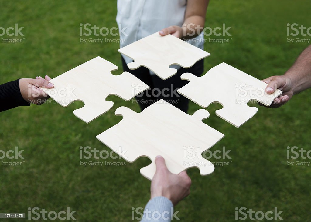 Four different people connecting large puzzle pieces stock photo