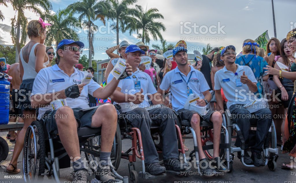 Four disabled man in wheelchair distributing leaflets of Lei Seca during Bloco Orquestra Voadora in Flamengo Park, Carnaval 2017 stock photo