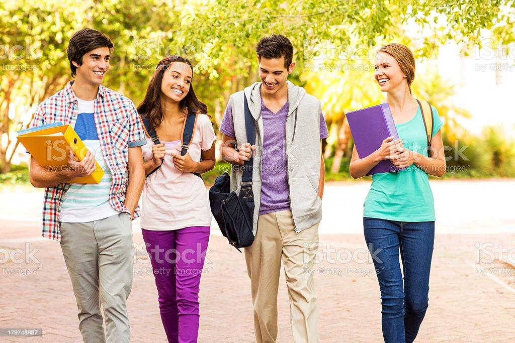 Four diverse students walking around campus stock photo