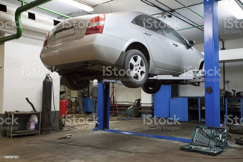 Four door sedan hoisted up in repair garage for inspection stock photo