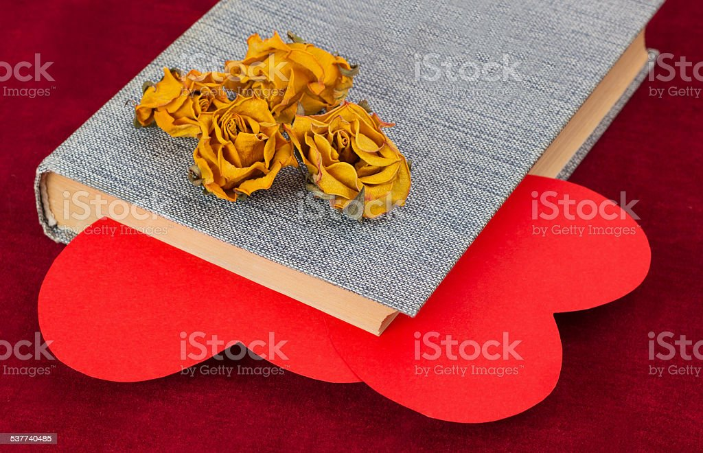 Four dried roses lying on the book with two hearts stock photo