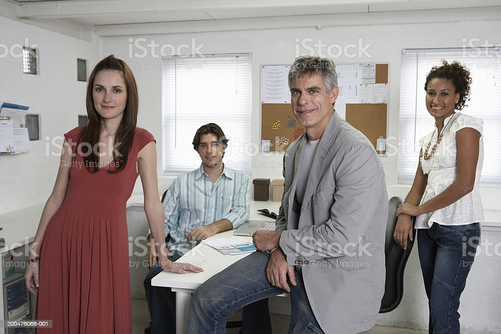Four executives in office, smiling, portrait stock photo