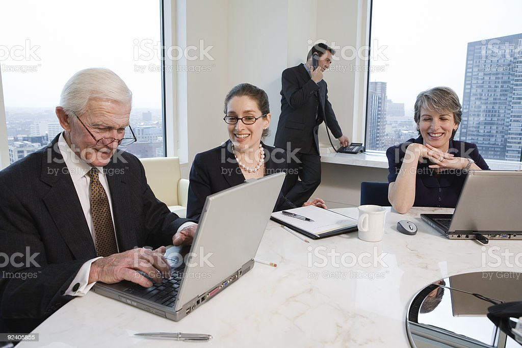 Four executives meeting with laptops in a conference room. royalty-free stock photo