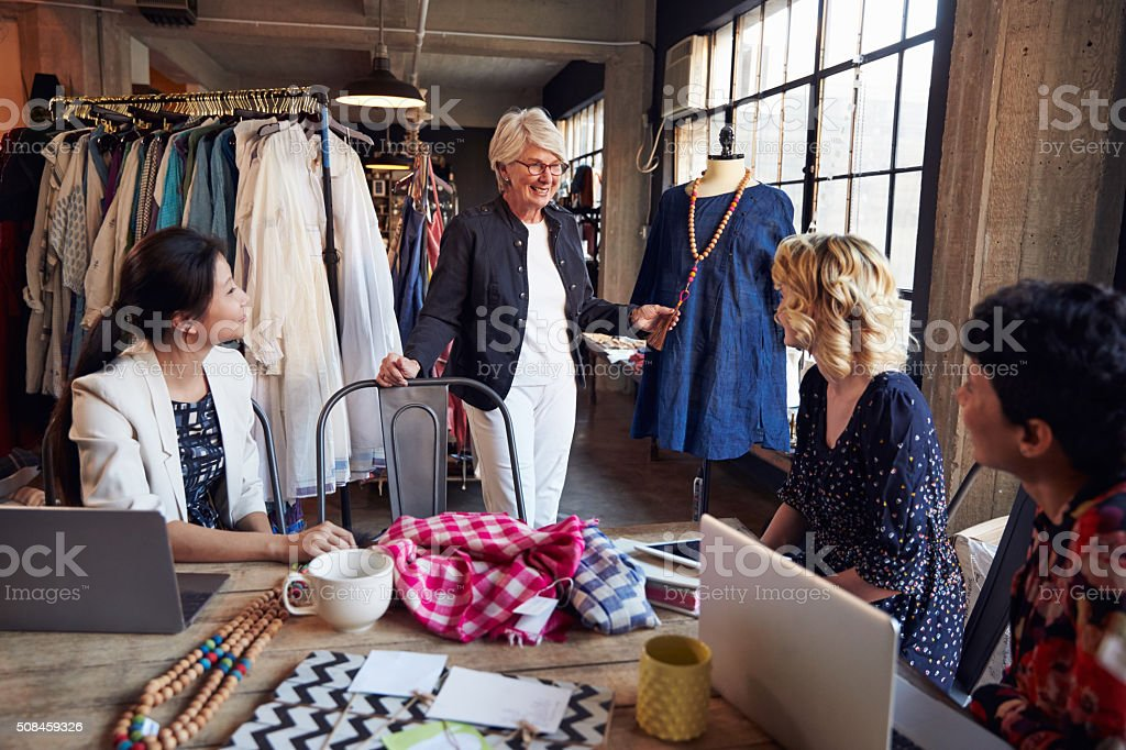 Four Fashion Designers In Meeting Discussing Garment stock photo