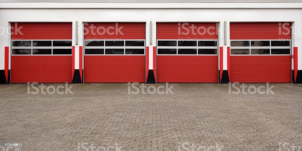 Four fed garage doors lined symmetrically stock photo