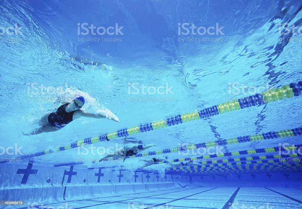 Four female professional participants racing in pool stock photo