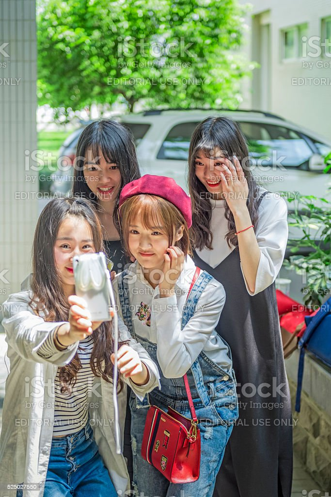 Four female students to take pictures as souvenirs. stock photo