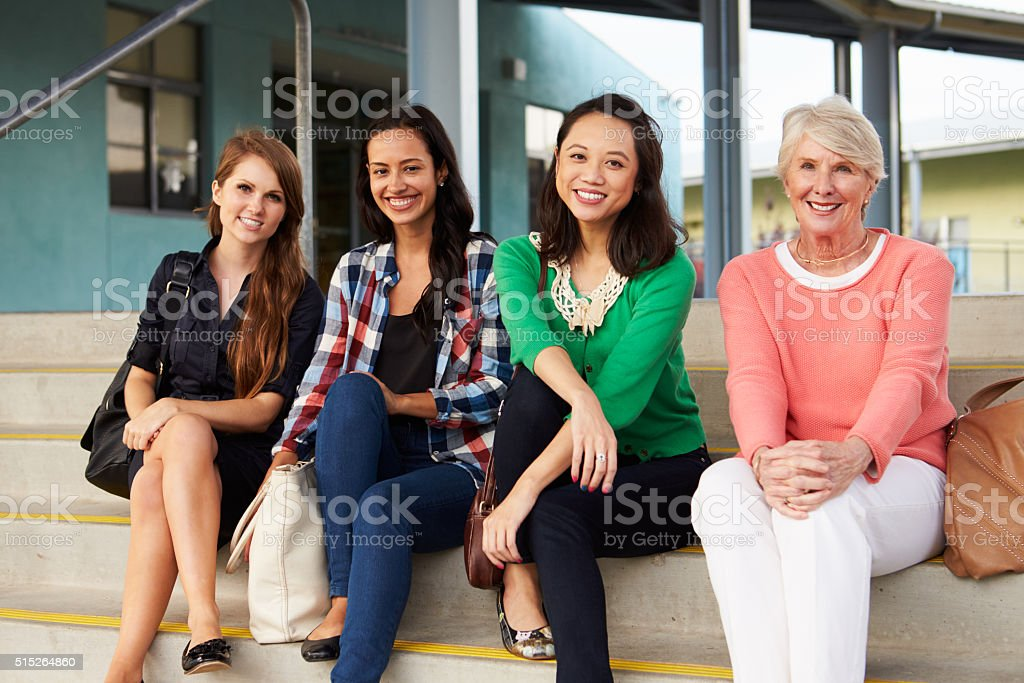 Four female teachers sitting on steps at entrance of school stock photo
