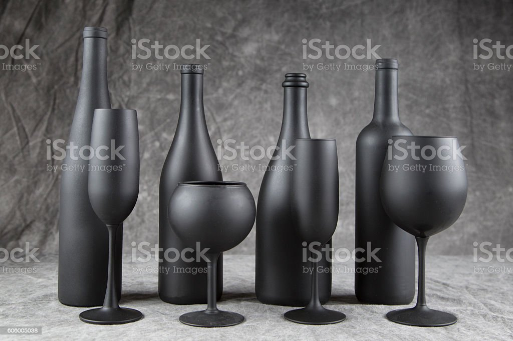 Four flat black wine bottles and stemware stock photo
