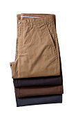 Four folded pairs of chinos in different colors