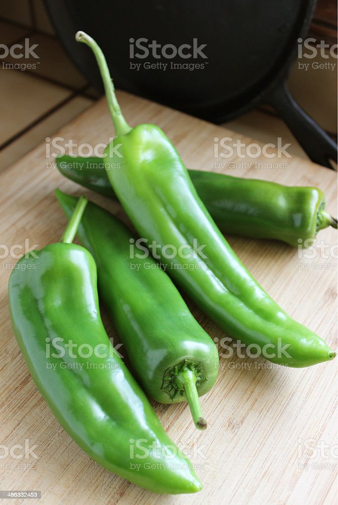 Four Fresh Green Chiles on Wooden Cutting Board stock photo