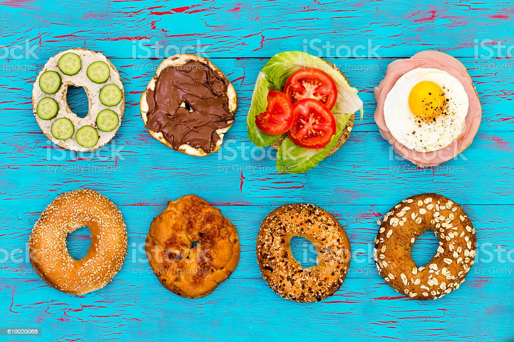 Four fresh sliced bagels with assorted filling stock photo