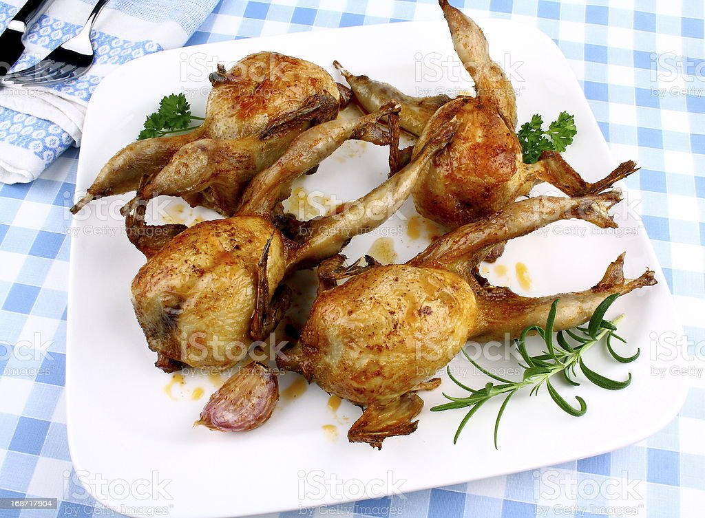 Four fried quail with gravy, garlic and rosemary, top view royalty-free stock photo