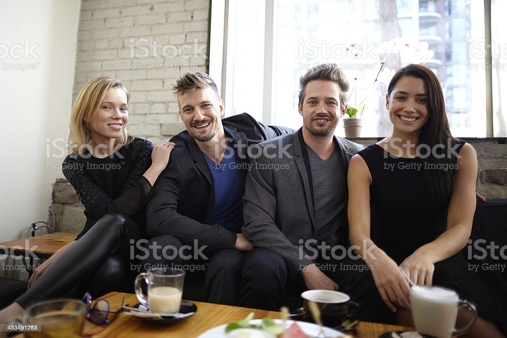 Four friends at restaurant eating and smiling royalty-free stock photo