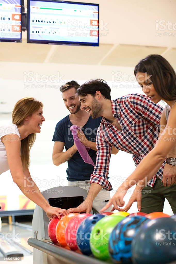 Four Friends Bowling Together. stock photo