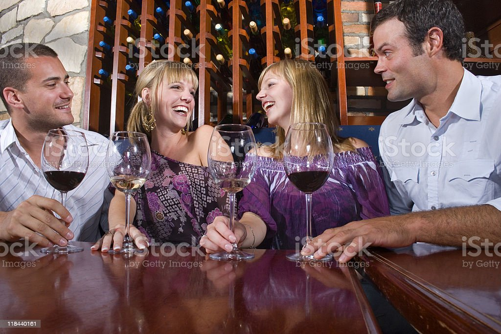 Four friends celebrating and drinking wine stock photo