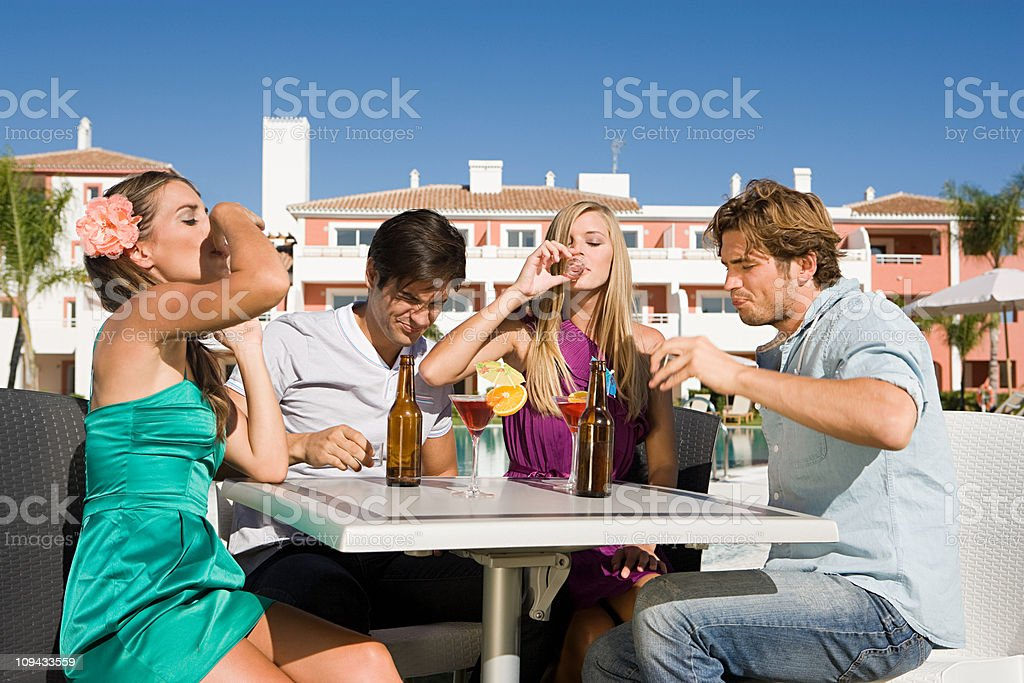 Four friends drinking shots on holiday stock photo