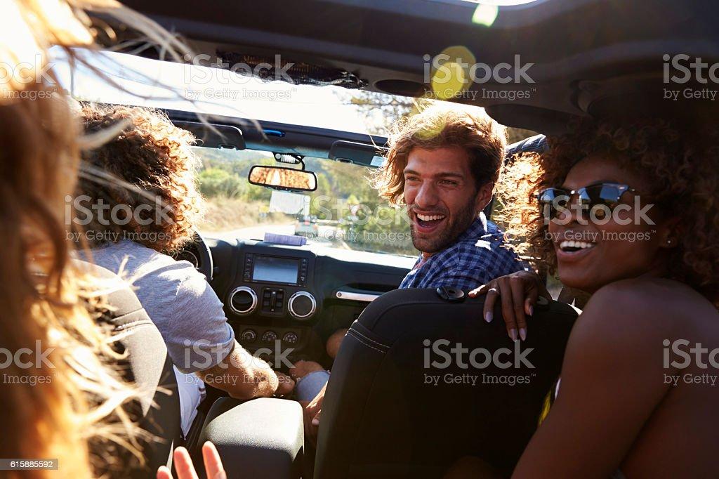 Four friends driving in an open top car, rear passenger stock photo