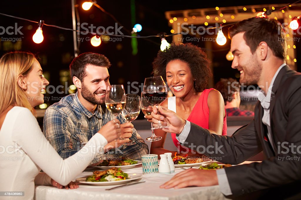 Four friends eating dinner at rooftop restaurant stock photo