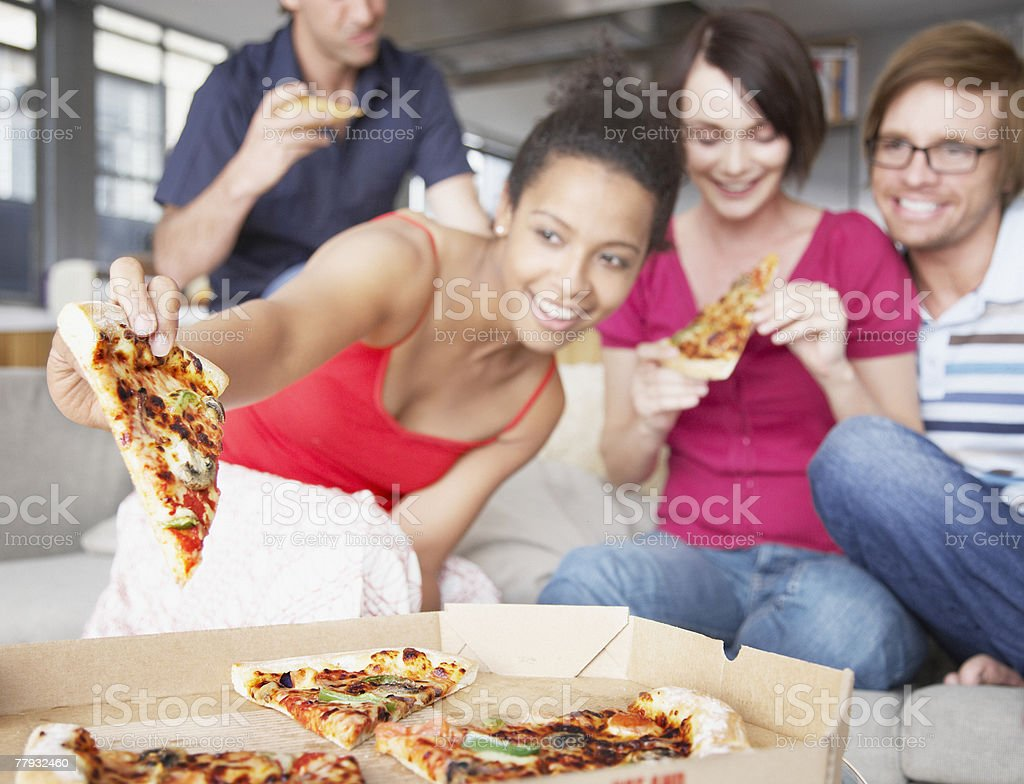 Four friends eating pizza in living room royalty-free stock photo