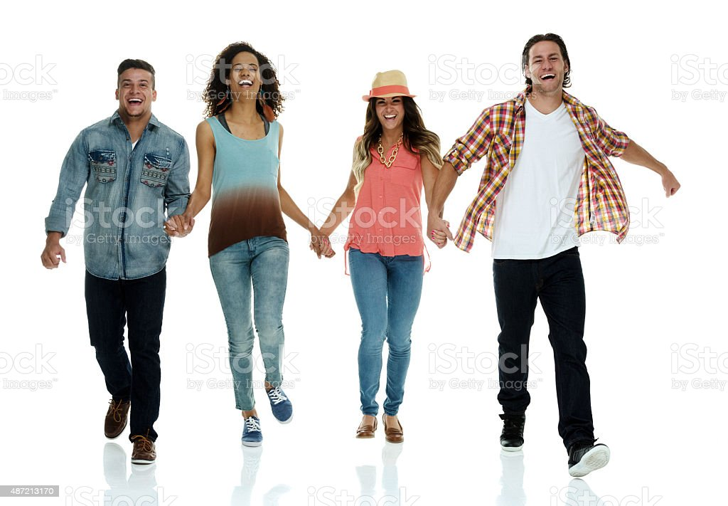 Four friends holding hands and walking fast stock photo