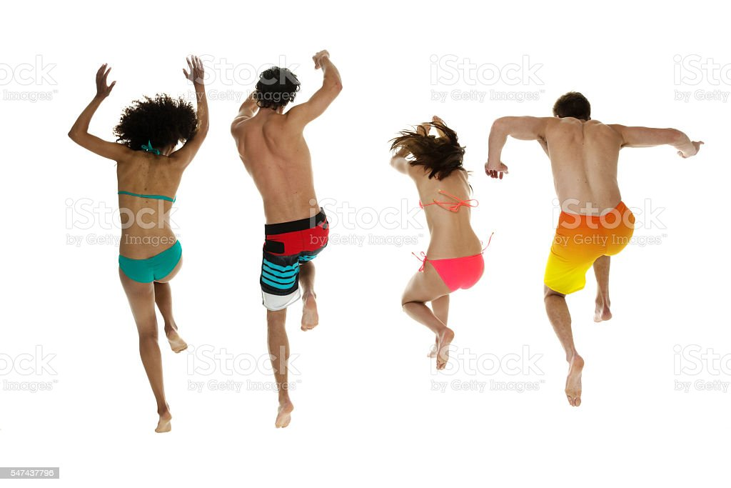 Four friends in swimwear and jumping stock photo