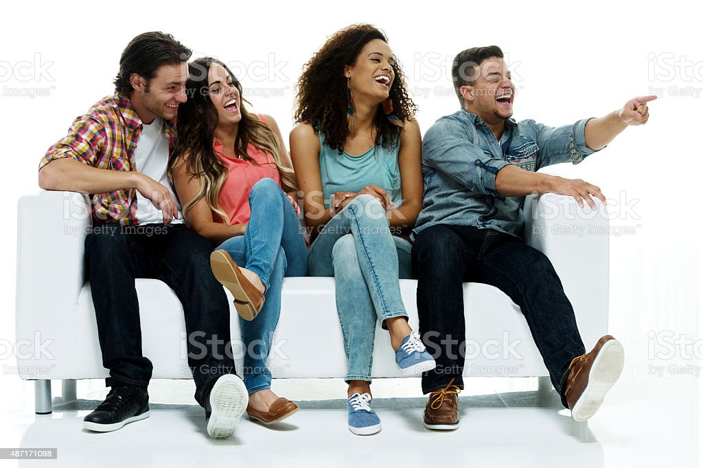 Four friends on couch and pointing stock photo