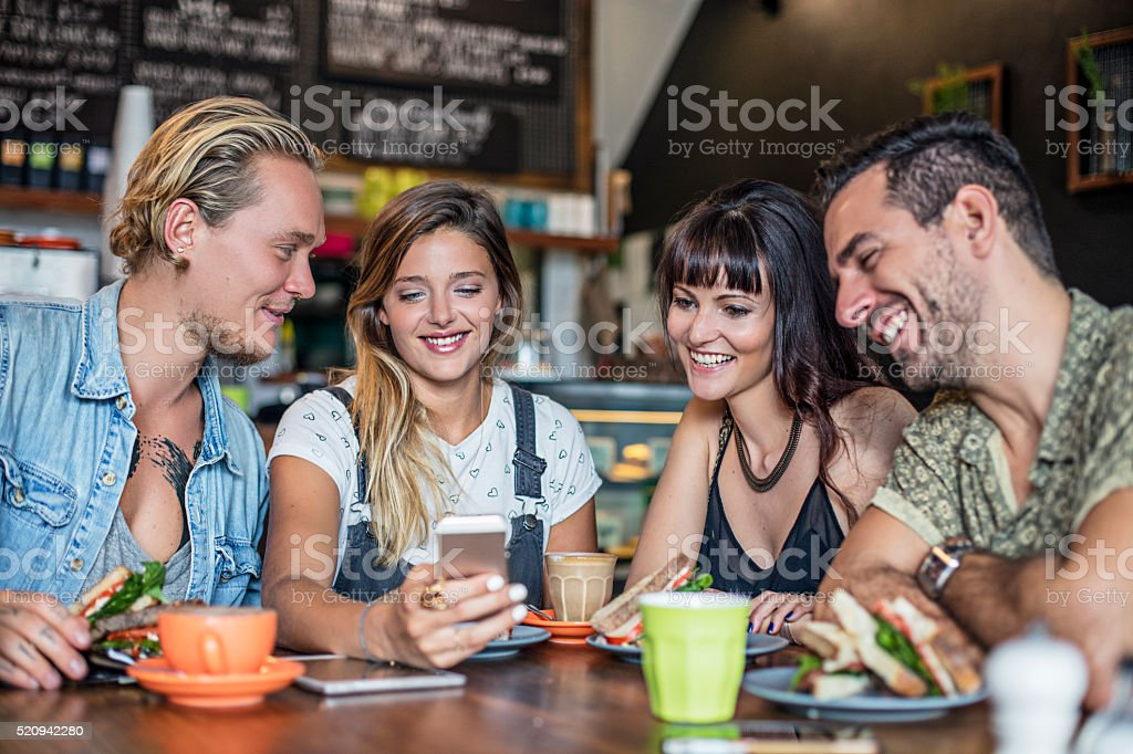 Four friends posting on social media in a coffee shop stock photo