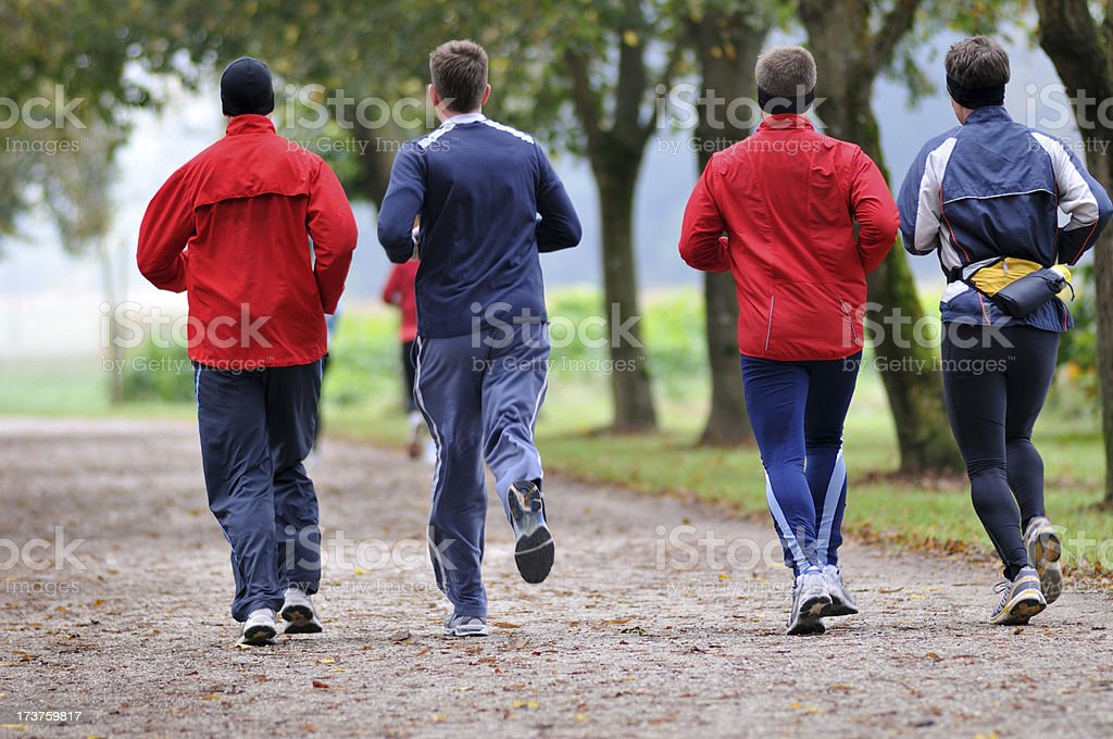 Four Friends running in nature stock photo