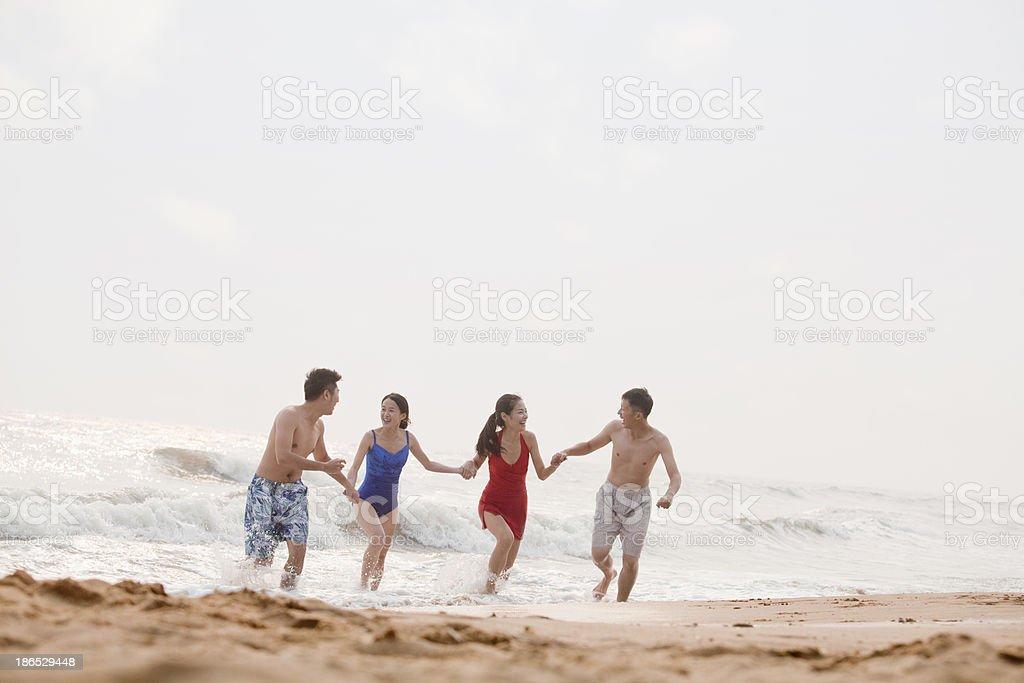 Four friends running on a sandy beach stock photo