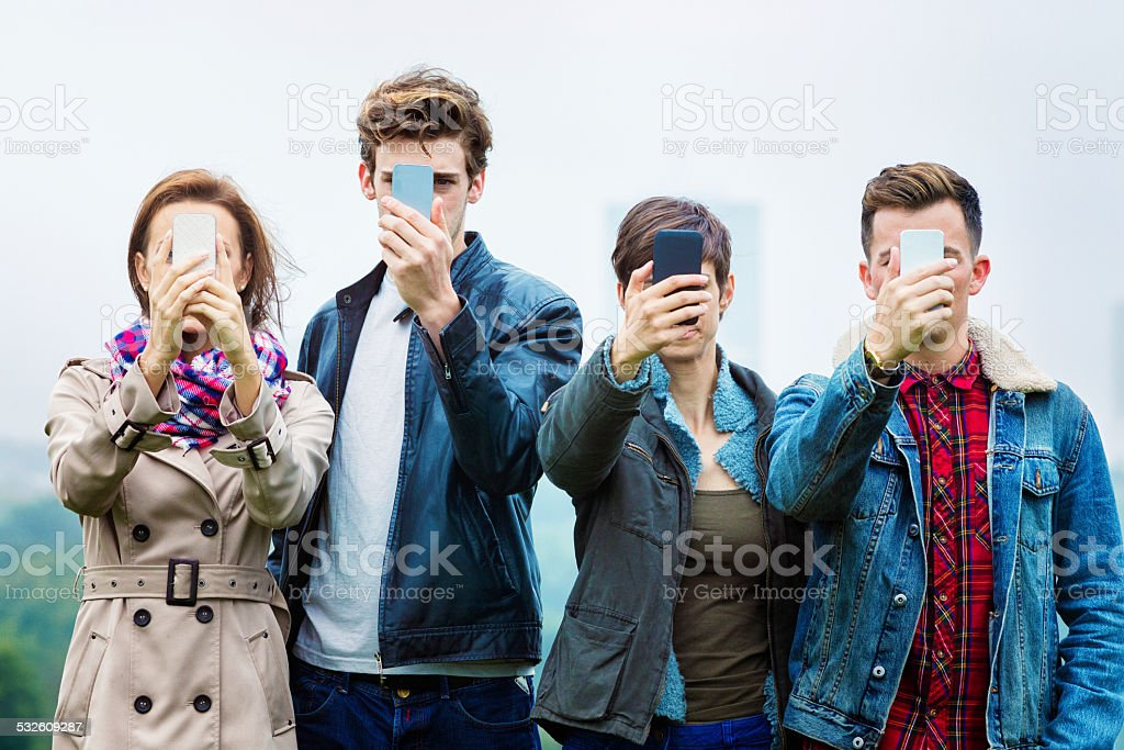 Four friends shooting selfies on their mobile phones stock photo