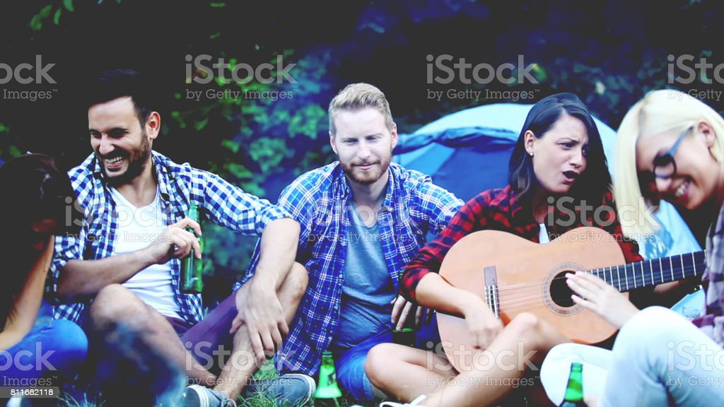Four friends sitting next to campfire and singing song stock photo