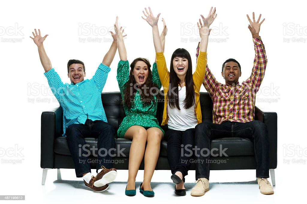 Four friends sitting of sofa stock photo