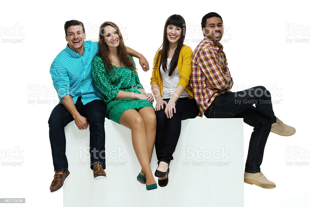 Four friends sitting on box stock photo