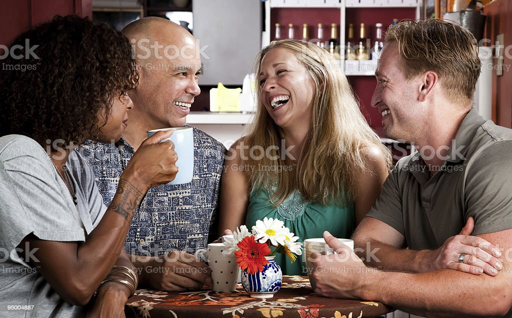 Four friends smiling and laughing while drinking coffee stock photo