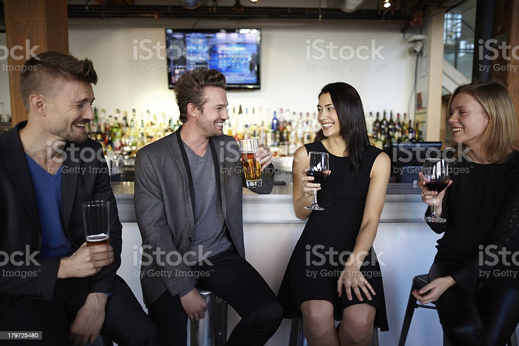 Four friends socializing and drinking at a bar counter smiling royalty-free stock photo
