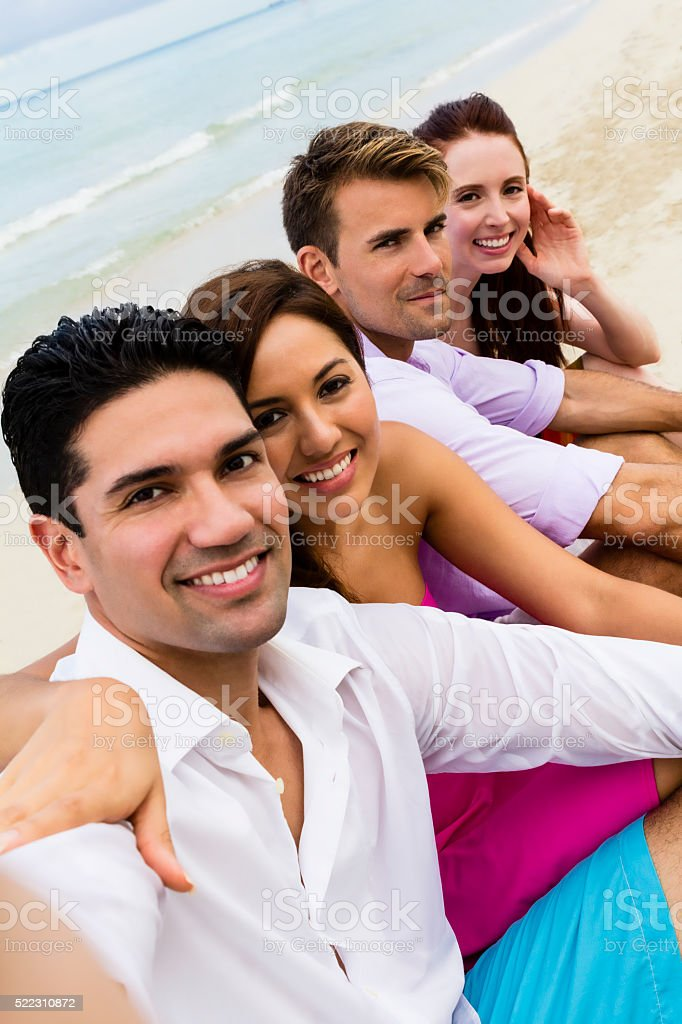Four friends taking selfie sitting on beach sand, vertical stock photo