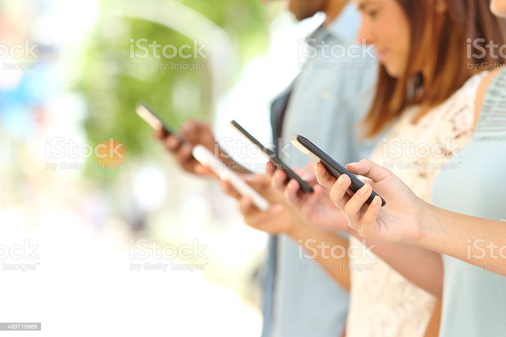 Four friends texting in their smart phones stock photo