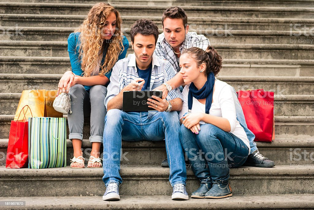 Four friends using a tablet sitting on staircase royalty-free stock photo