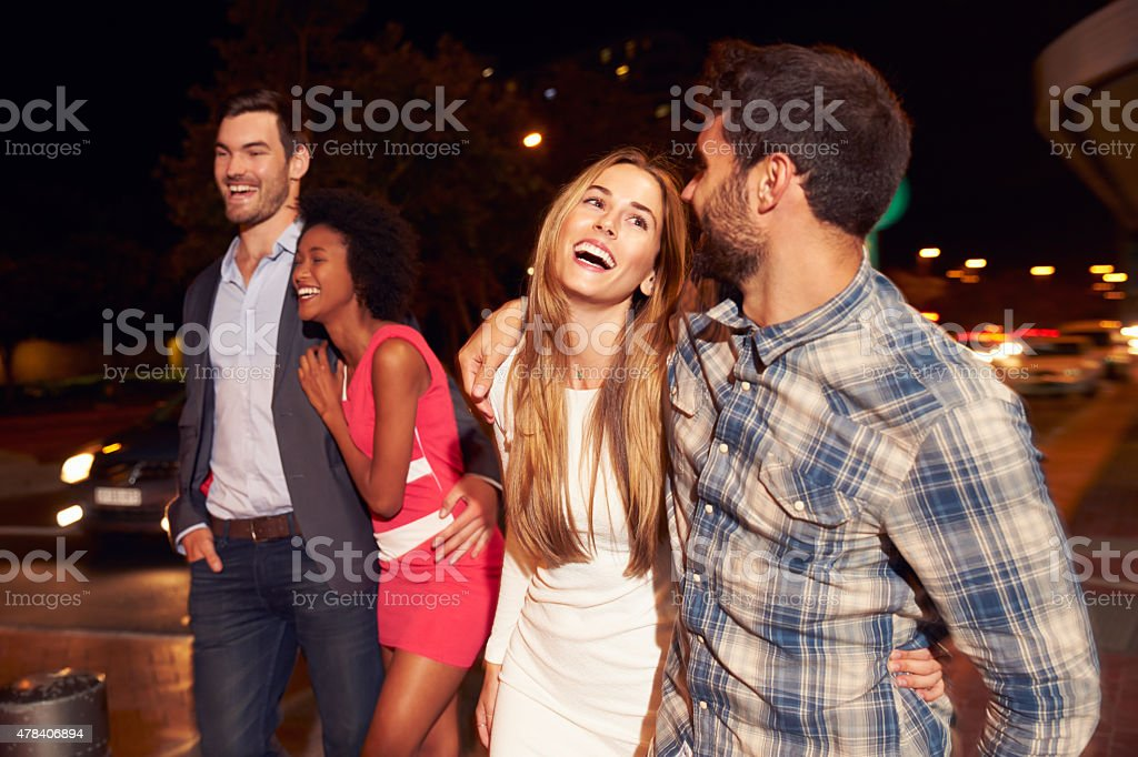 Four friends walking through town together at night stock photo