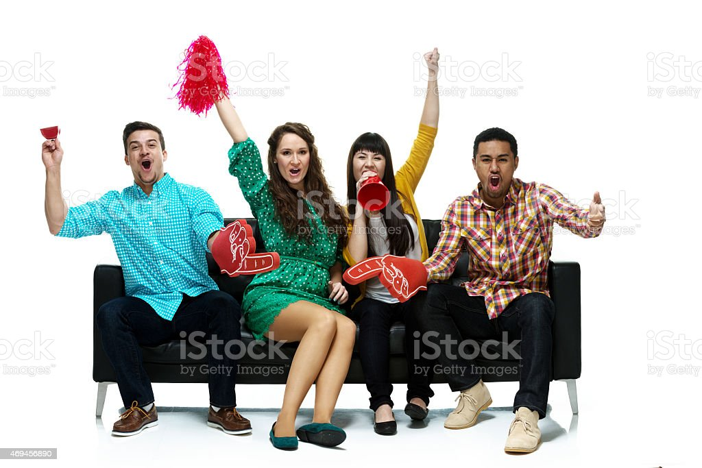 Four friends watching tv and cheering stock photo