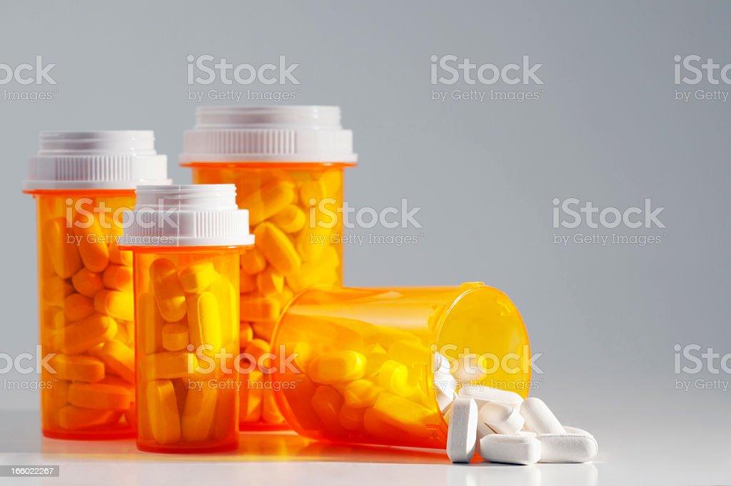 Four full prescription bottles with one spilling medication stock photo