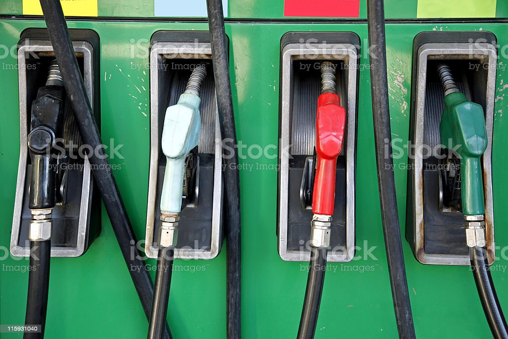Four gas pumps with black, white, red and green nozzles royalty-free stock photo