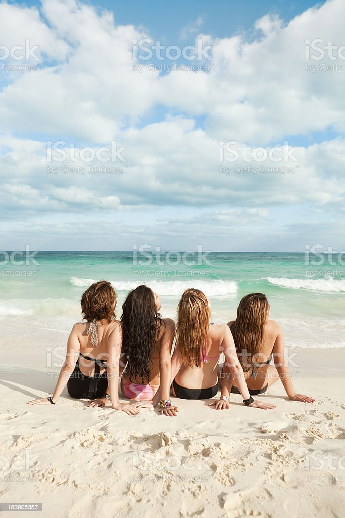 Four Girl Friends Sitting on Riviera Maya Beach Sand, Mexico royalty-free stock photo