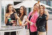 Four girlfriends having drinks outdoors