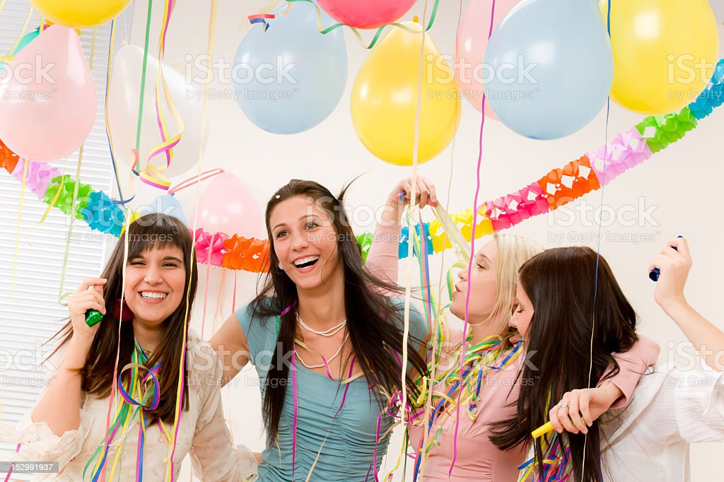 Four girls celebrating with balloons and streamers stock photo