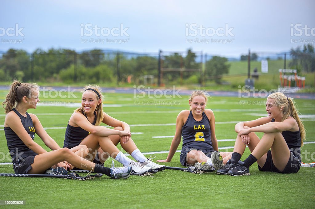 Four Girls Chat at Dusk After Lacrosse Practice stock photo
